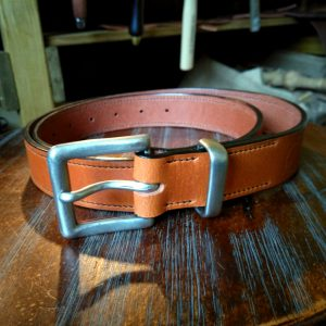 A belt in tan with a full length black stitch using a salvaged matt buckle