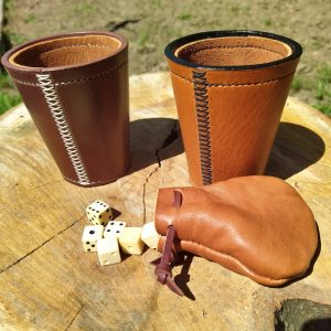 Dice cups in dark brown and tan with cream and black cross stitching and sheepskin lining with a sheepskin dice pouch and hand carved bone dice