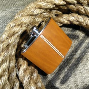 Hip flask wrapped in tan leather with a cream cross stitch
