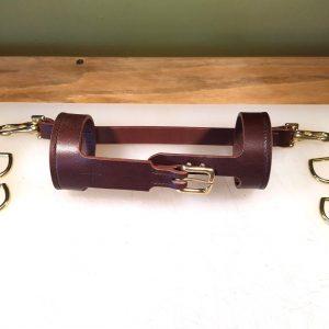 Speaker sling in dark brown with brass metalwork to hold bluetooth speaker in van